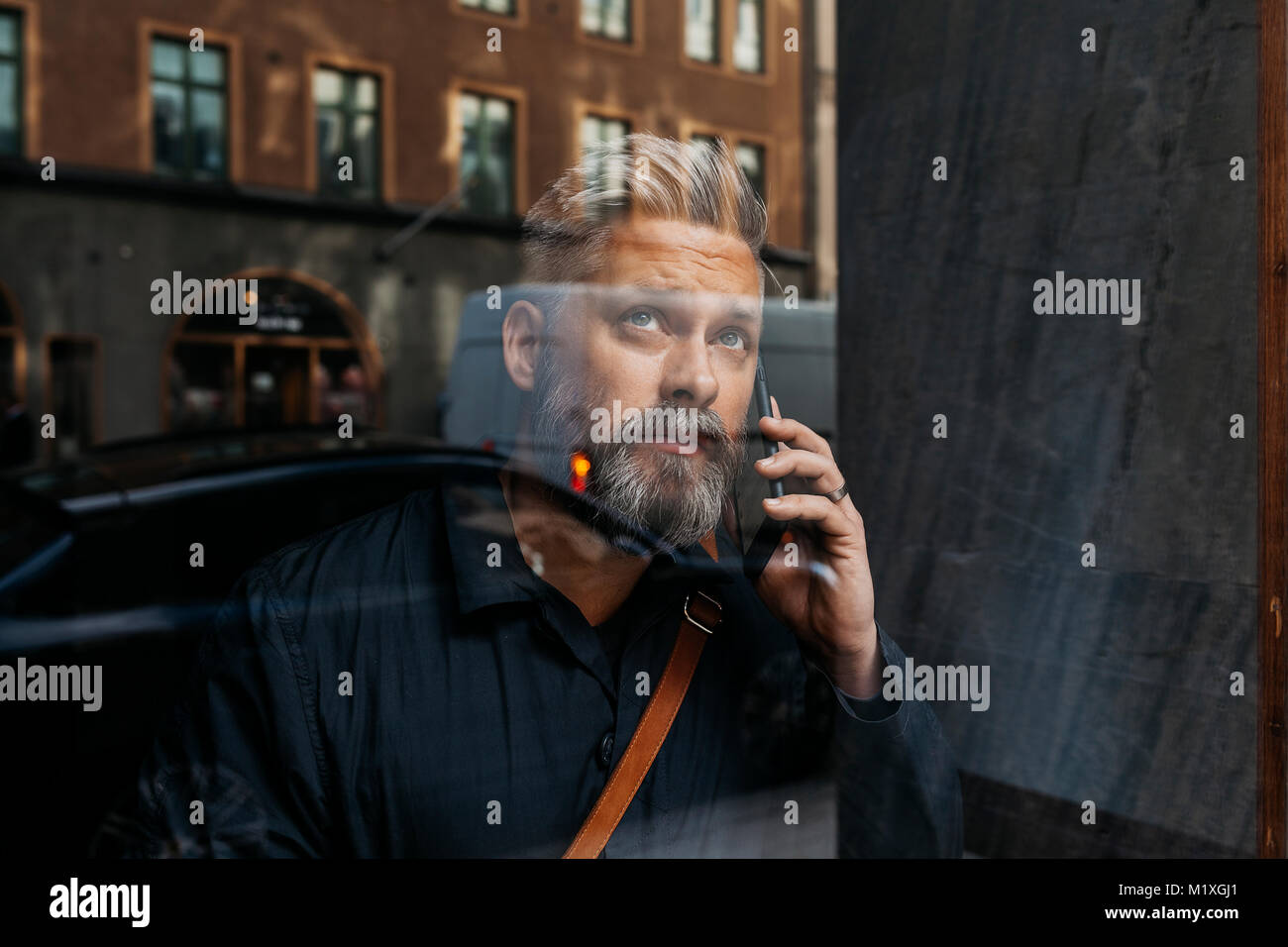 Man on smart phone through window in Sweden - Stock Image