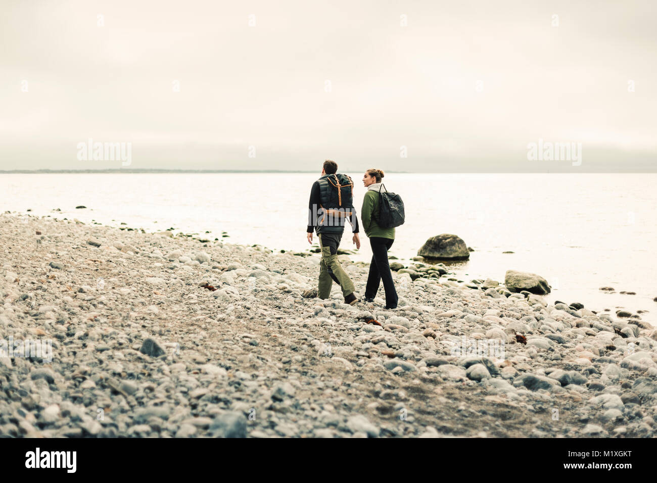 Rear view of couple walking along rocky coastline in Stockholm, Sweden - Stock Image