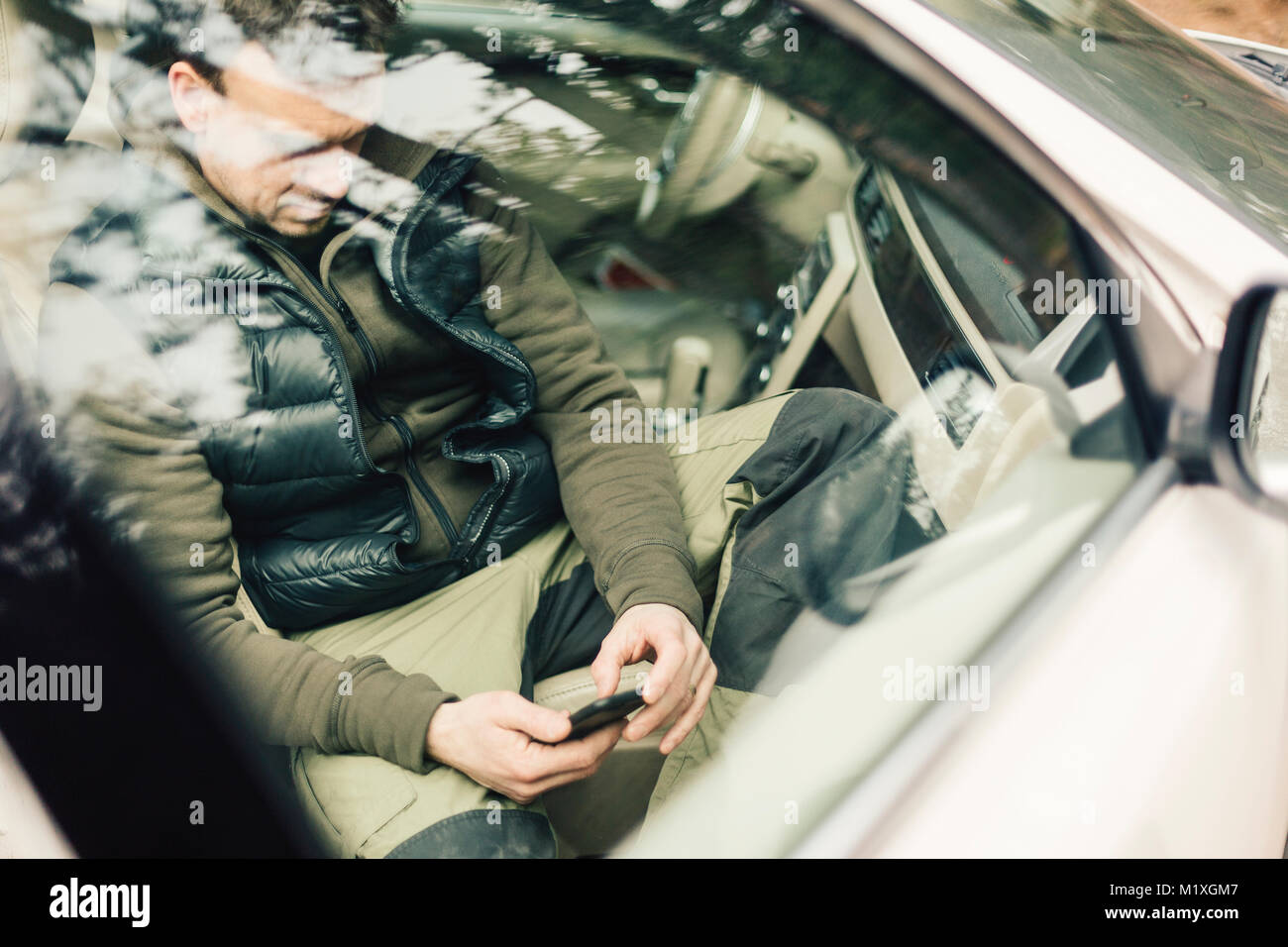Man on smart phone behind car window in Sweden - Stock Image