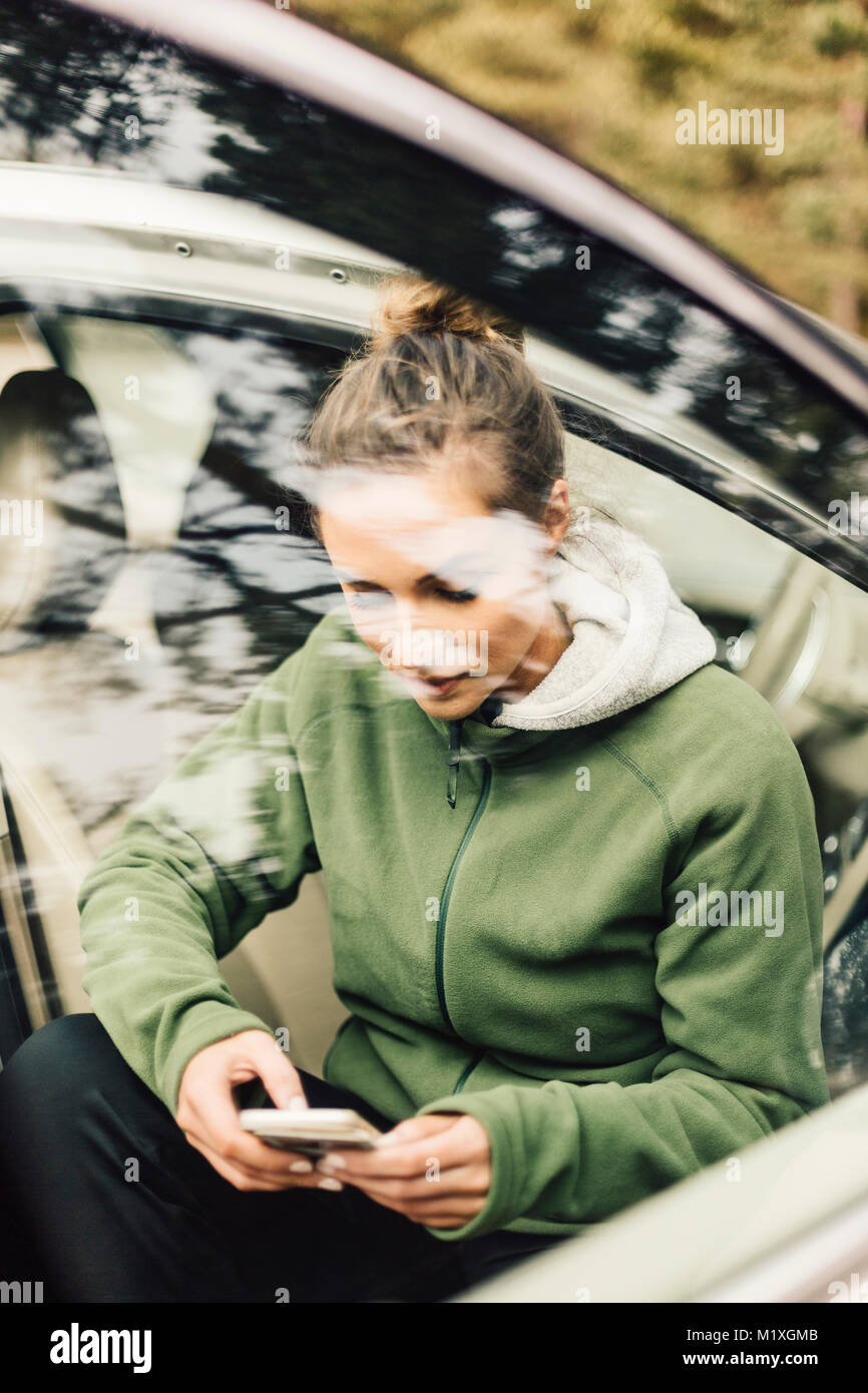 Young woman sitting in car on smart phone in Sweden - Stock Image