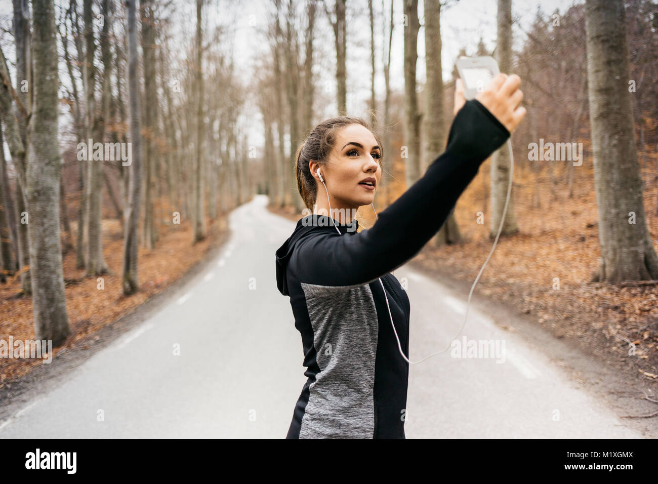 Young woman taking selfie on rural road in Sodermanland, Sweden Stock Photo