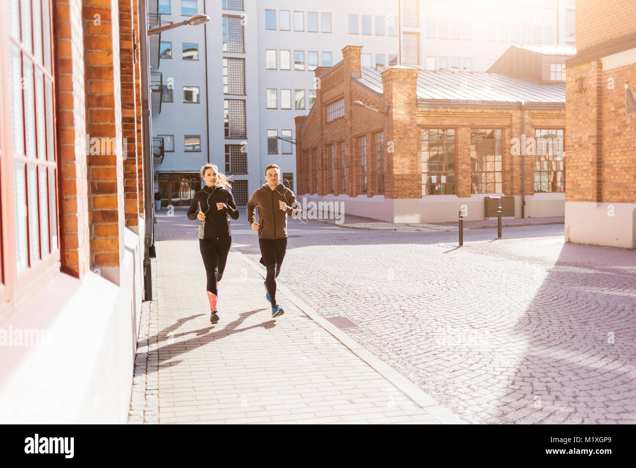 Man and woman running along street in Stockholm, Sweden Stock Photo