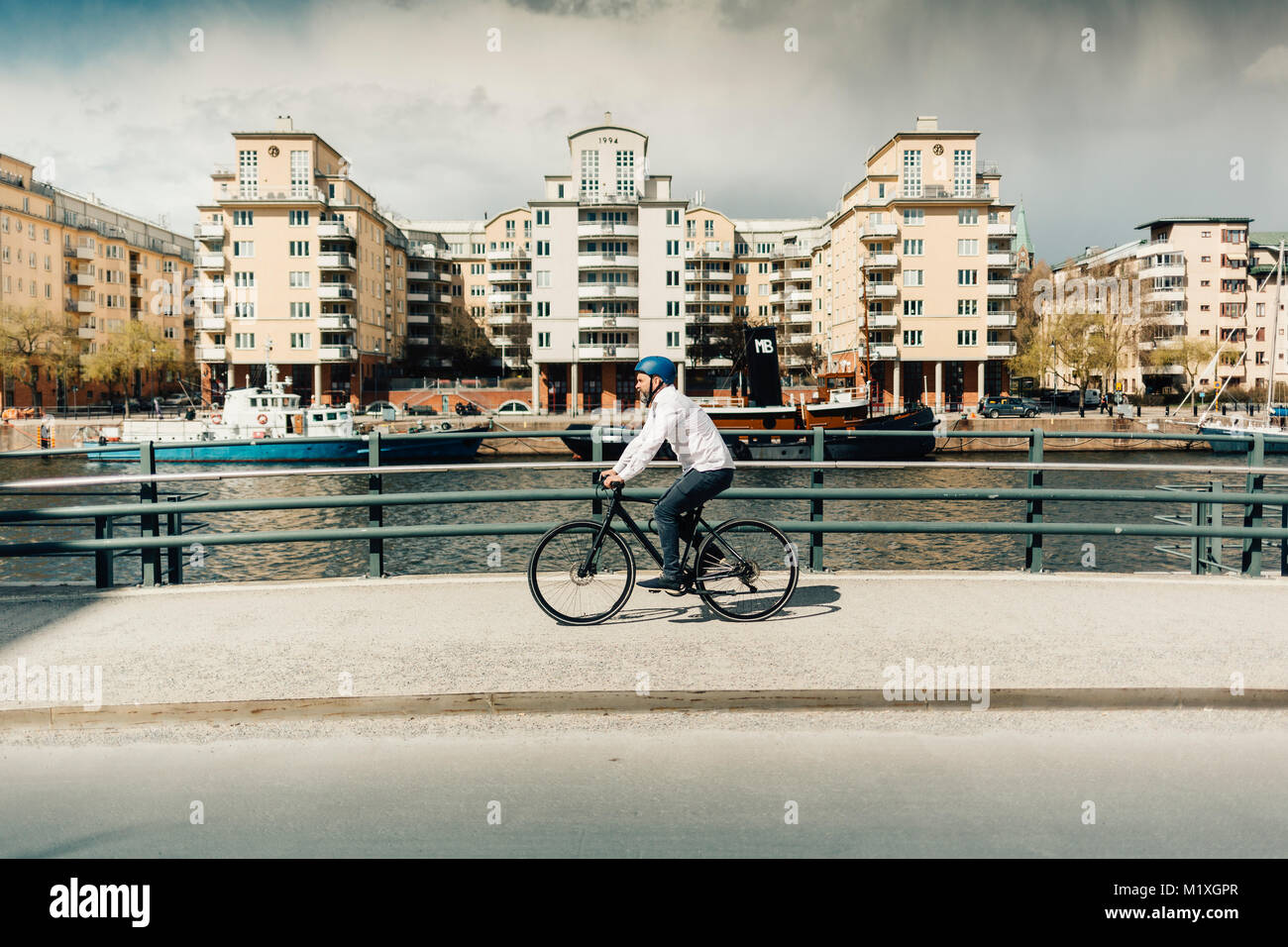 Man bicycling on street in Stockholm, Sweden - Stock Image
