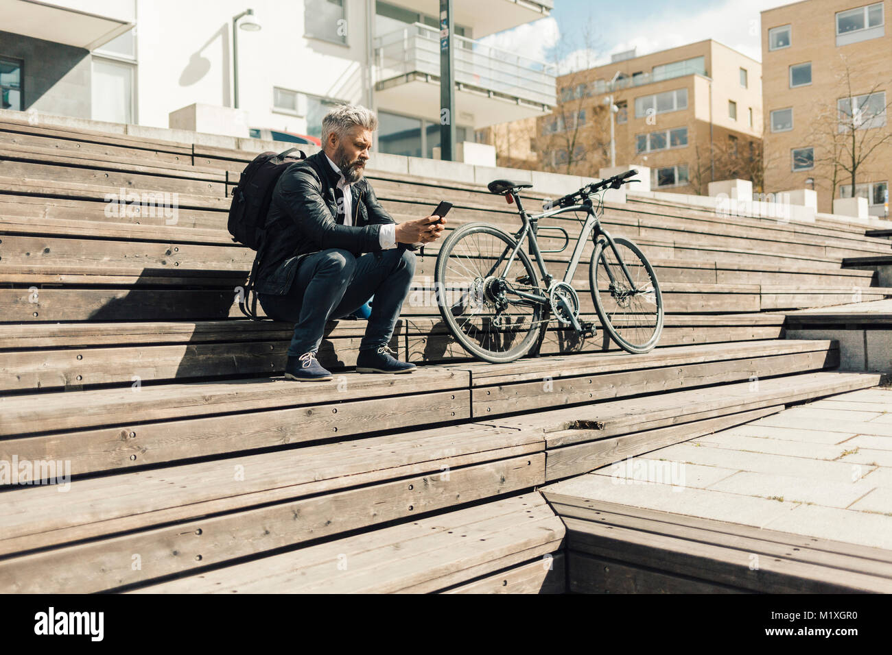 Man on staircase with bicycle in Sodermanland, Sweden - Stock Image