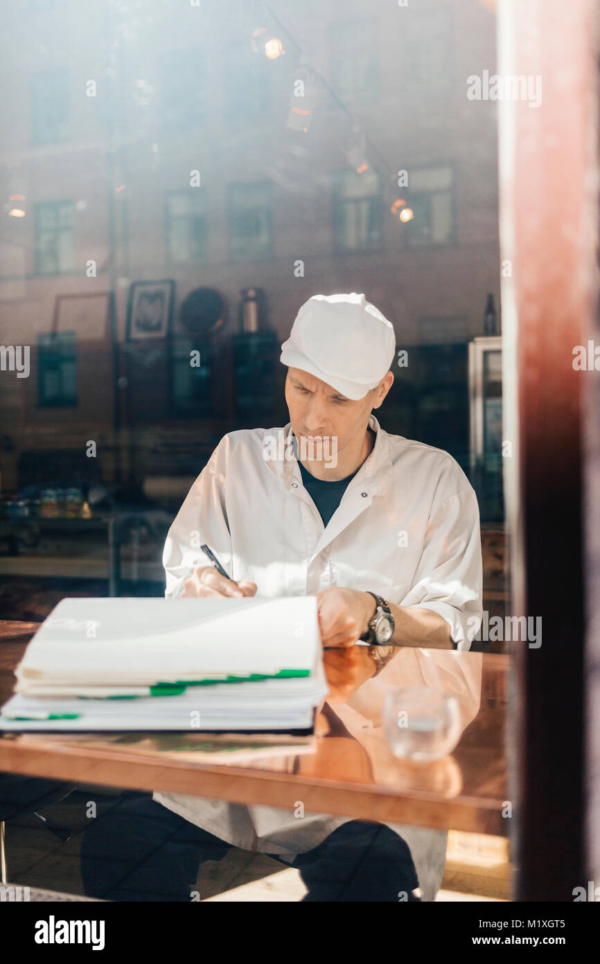 Butcher writing at window in Sweden - Stock Image