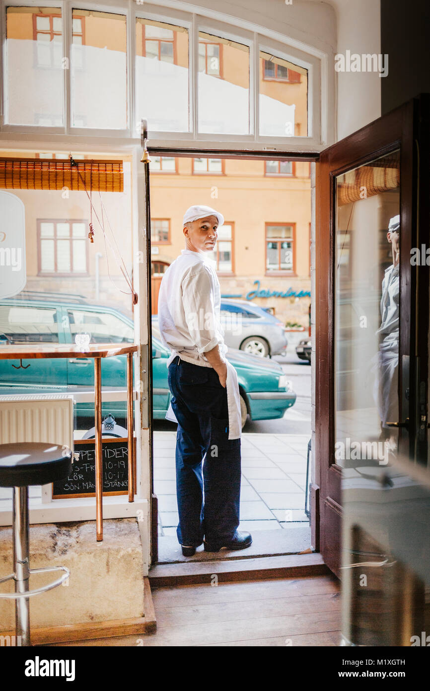 Butcher at doorway of store in Sweden - Stock Image