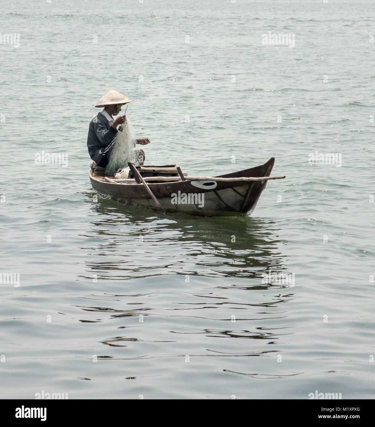 Vietnamese man fishing from small traditional fishing boat on the river Bon , Hoi An. - Stock Image