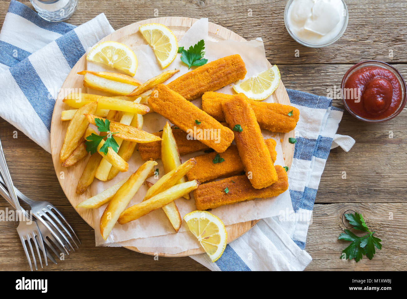 Fried Fish Sticks with French Fries. Fish Fingers over wooden background. Fish Sticks with fried potato and lemon - Stock Image