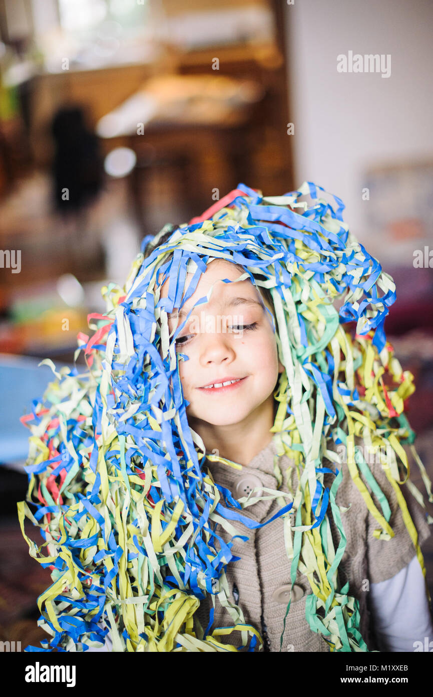 child little girl with streamers around his neck and head for the carnival party in his home - Stock Image