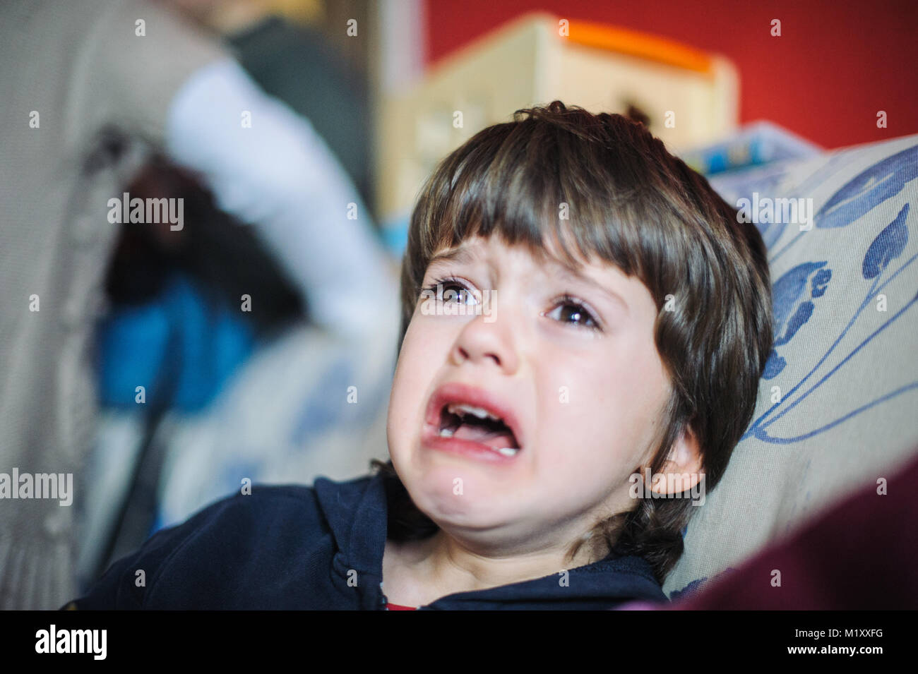 6 year old boy sad and crying in his home sitting on the couch - Stock Image