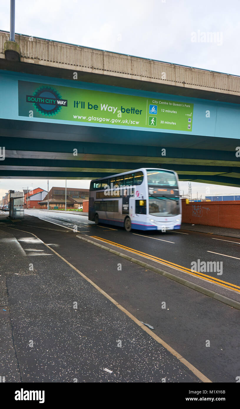 A bus driving underneath an M74 motorway in Glasgow south side,with motion blur. - Stock Image