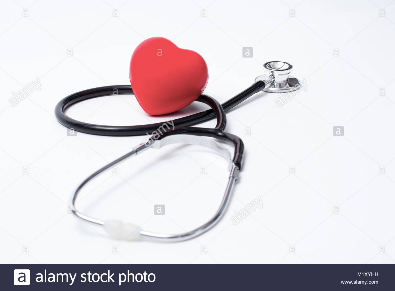 Medical stethoscope head and red toy heart lying on cardiogram chart closeup. Cardio therapeutist, pulse graph, - Stock Image
