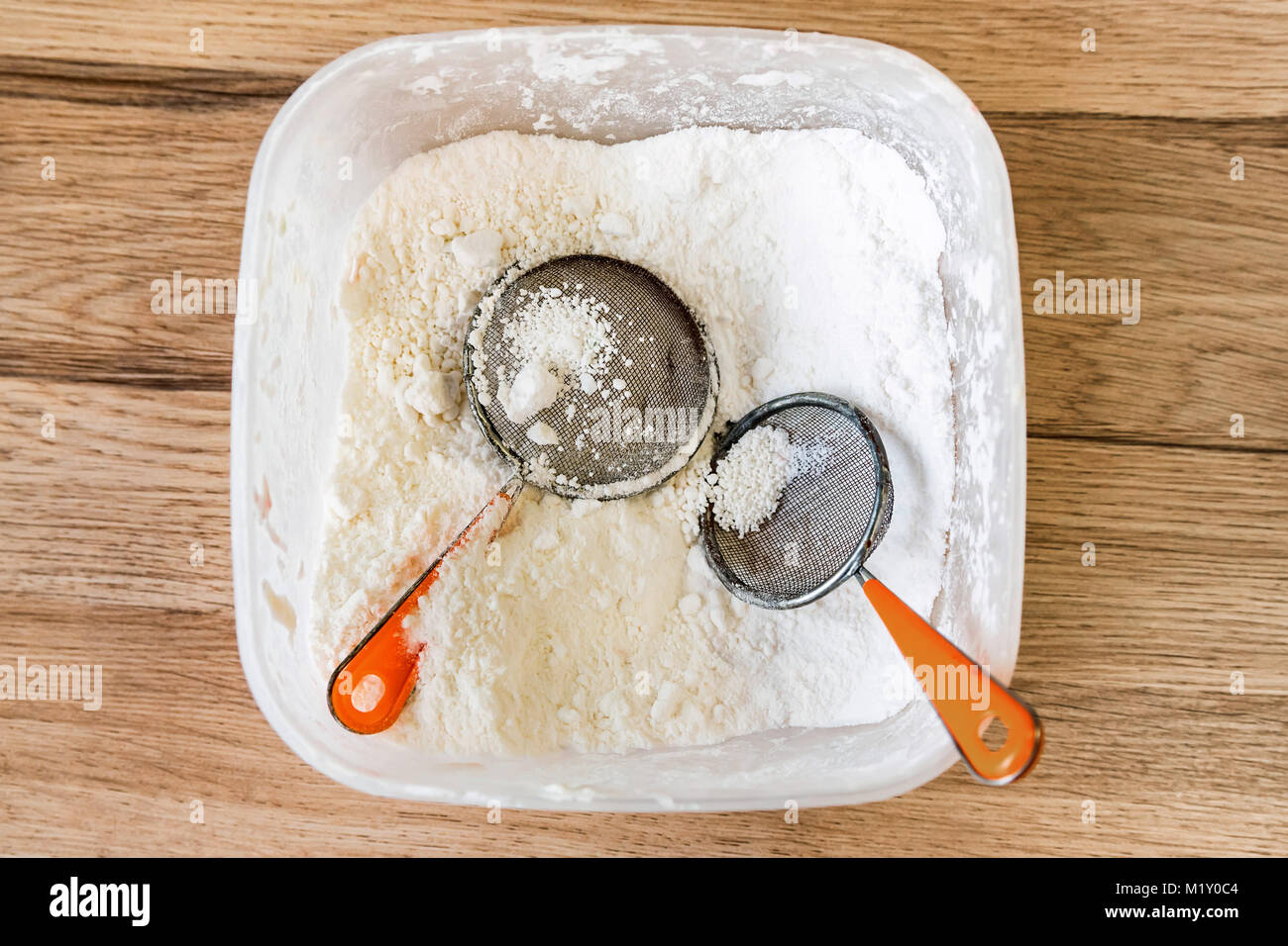 Sugar powder and two sifters in container - Stock Image