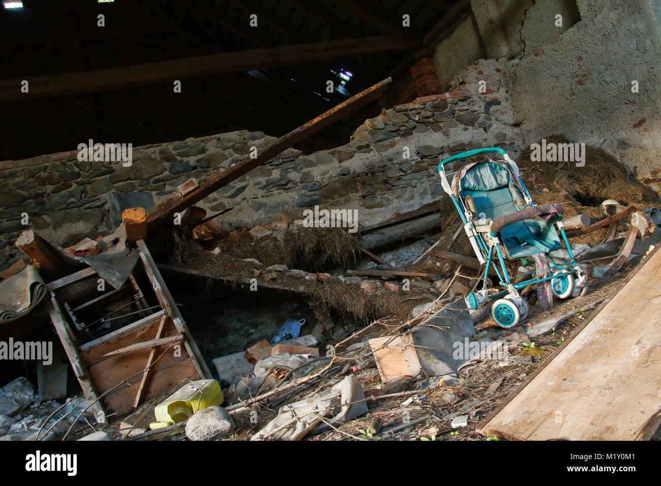 The interior of and old ruin is filled with a mess. An abandoned baby carriage can be seen. - Stock Image