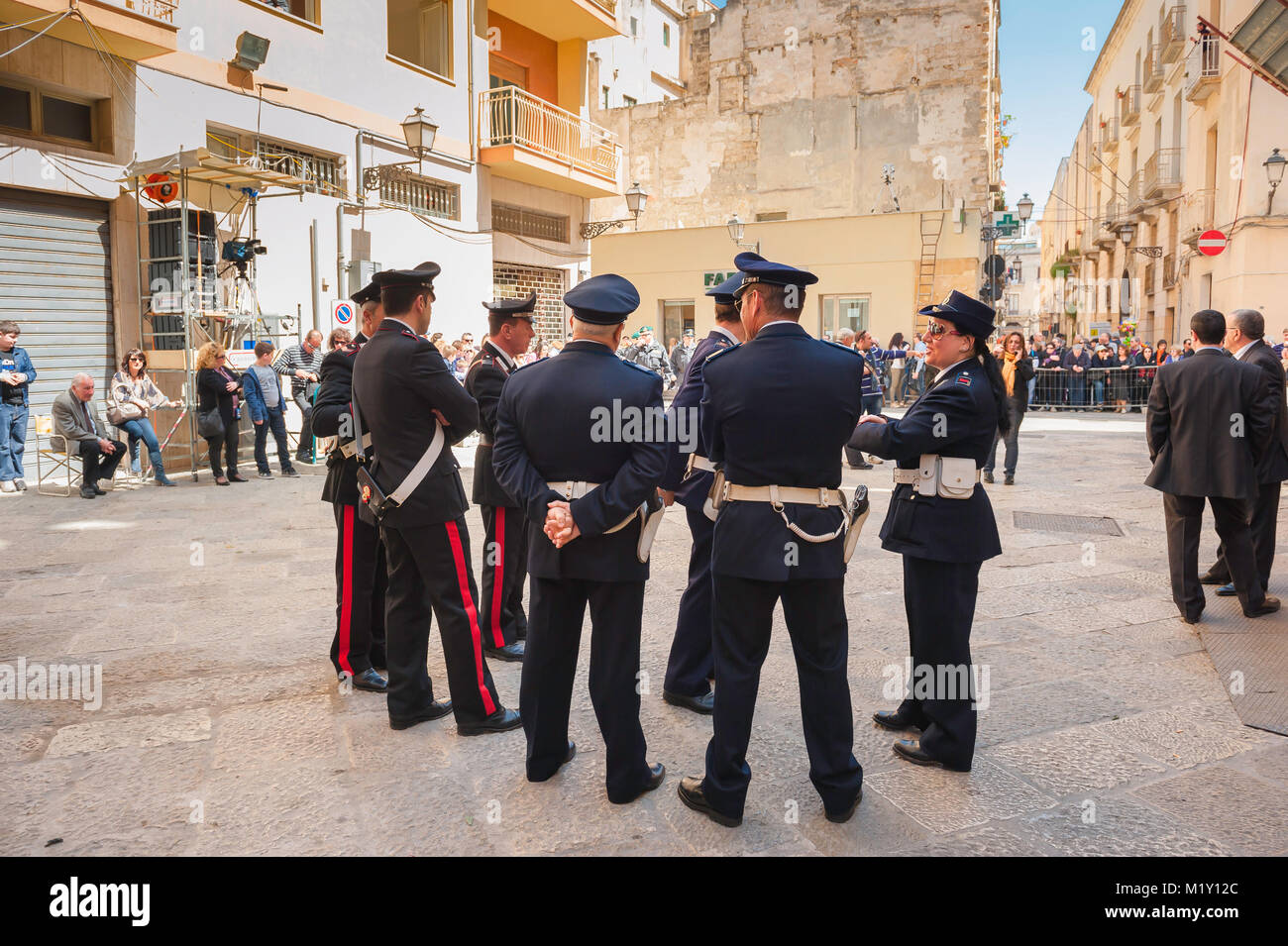 Trapani Easter, a group of Sicilian police officers in Trapani chat prior to the commencement of the Easter Procession - Stock Image