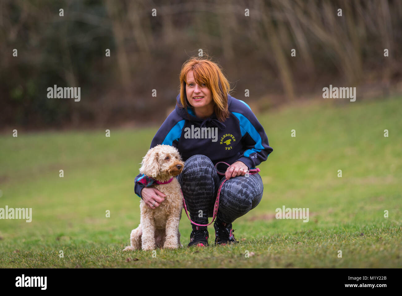 Little puppy terrier dog with its female owner in a park - Stock Image