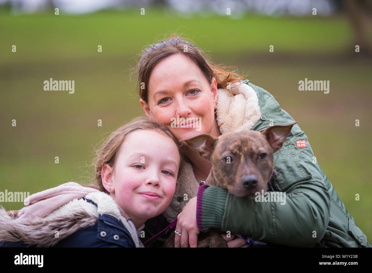Woman with her daughter and their pet staffordshire bull terrier dog in the park smiling - Stock Image