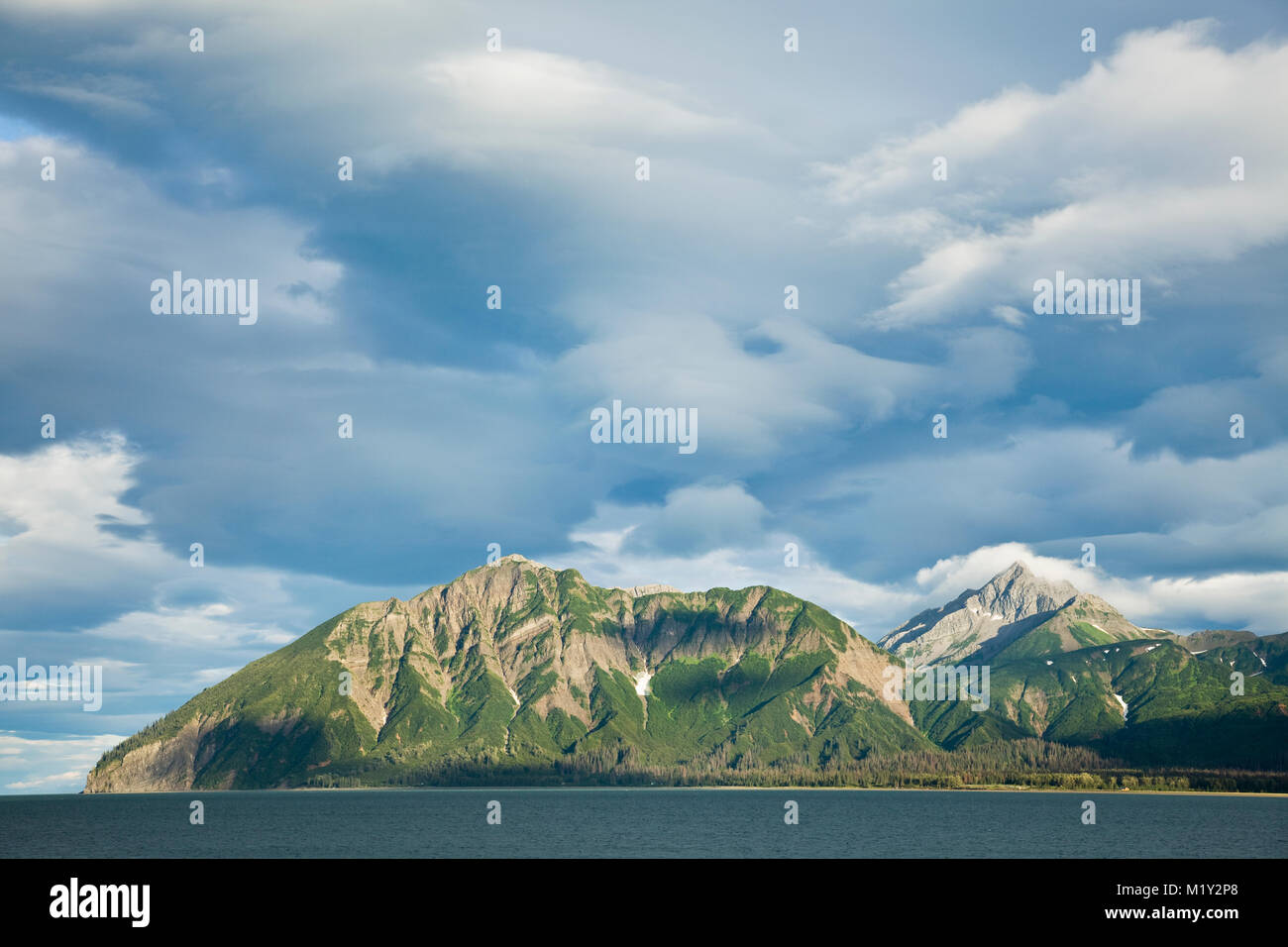 Dramatic evening light and clouds above Mount Chinitna and the Chigmit Mountains along Chinitna Bay in Lake Clark - Stock Image