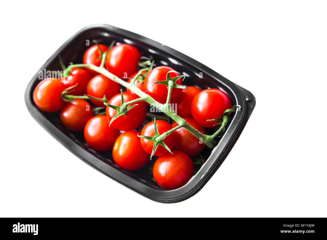 Ripe cherry tomatoes in plastic container against a white background - Stock Image