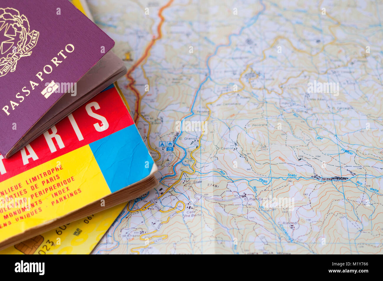Passport over a map and a credit card - Stock Image
