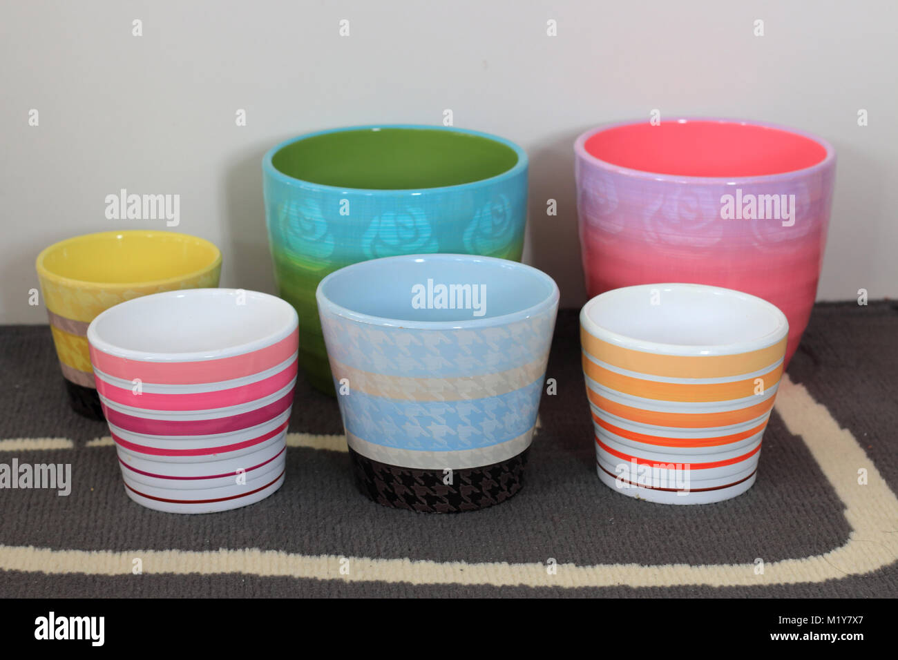 Colourful ceramic pot plants in different sizes - Stock Image