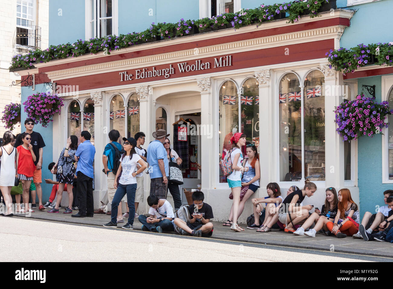Access to 'The Edinburgh Woollen Mill' shop opposite Windsor Castle made difficult by tourists blocking - Stock Image