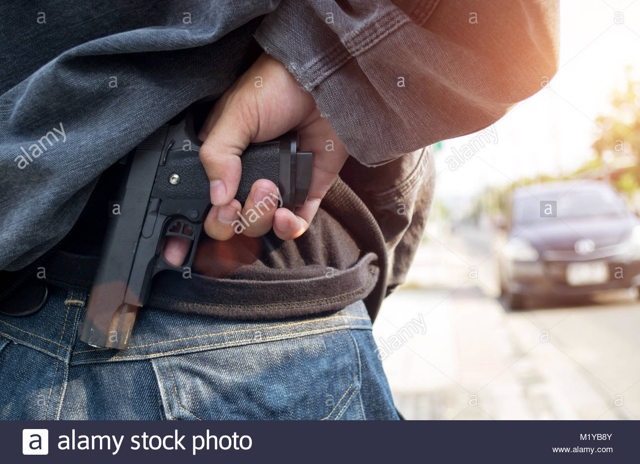 Male thief with pistol trying to steal car - Stock Image