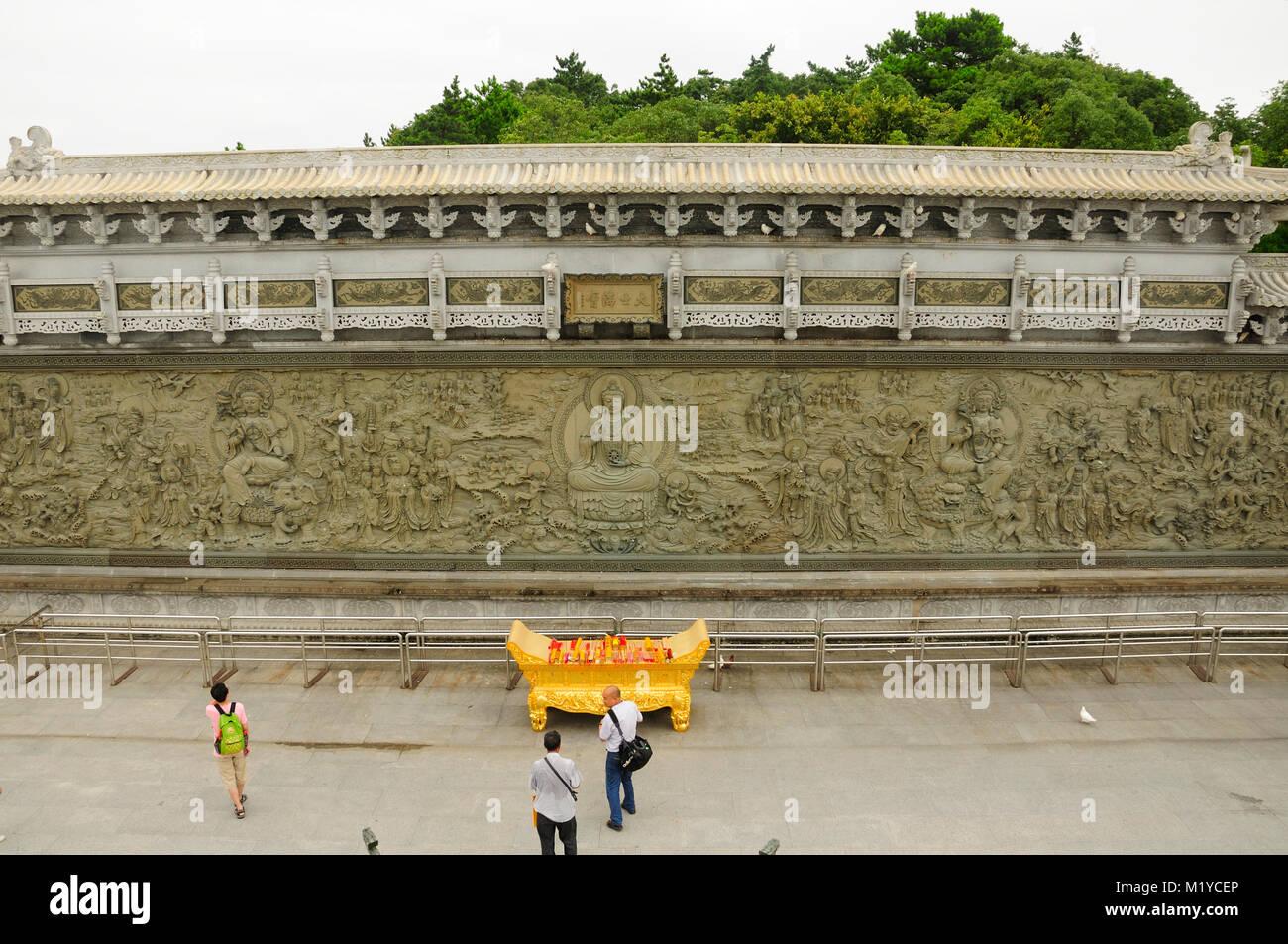 July 19, 2015.  Putuoshan, China.  A large Buddhist religious  mural and Chinese tourists on the island of Putuoshan - Stock Image