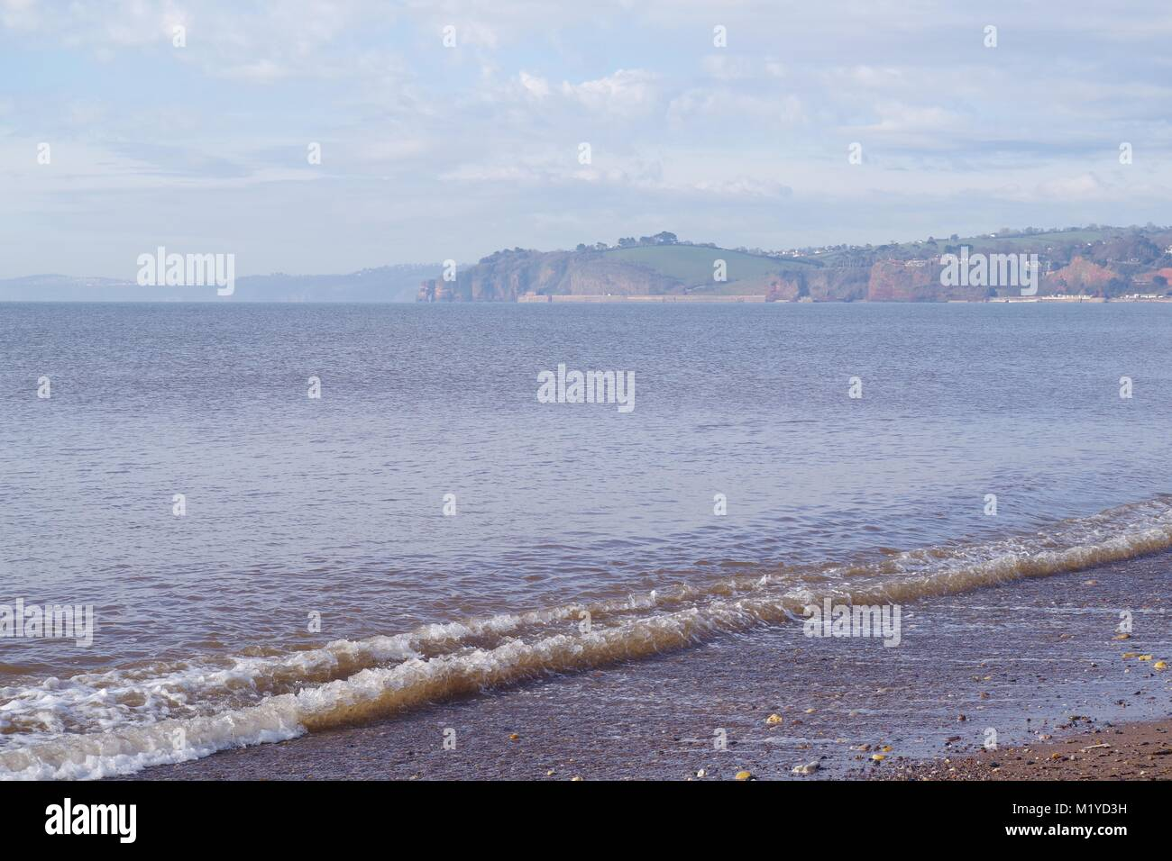 Calm Spring Morning overlooking a Falt Tranquil Sea of the English Channel from Dawlish Beach, Red Cliffs and Devon - Stock Image