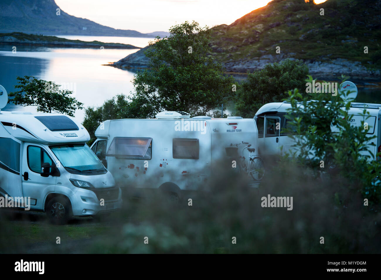Three RVs parked overnight nearby the sea or a lake. - Stock Image