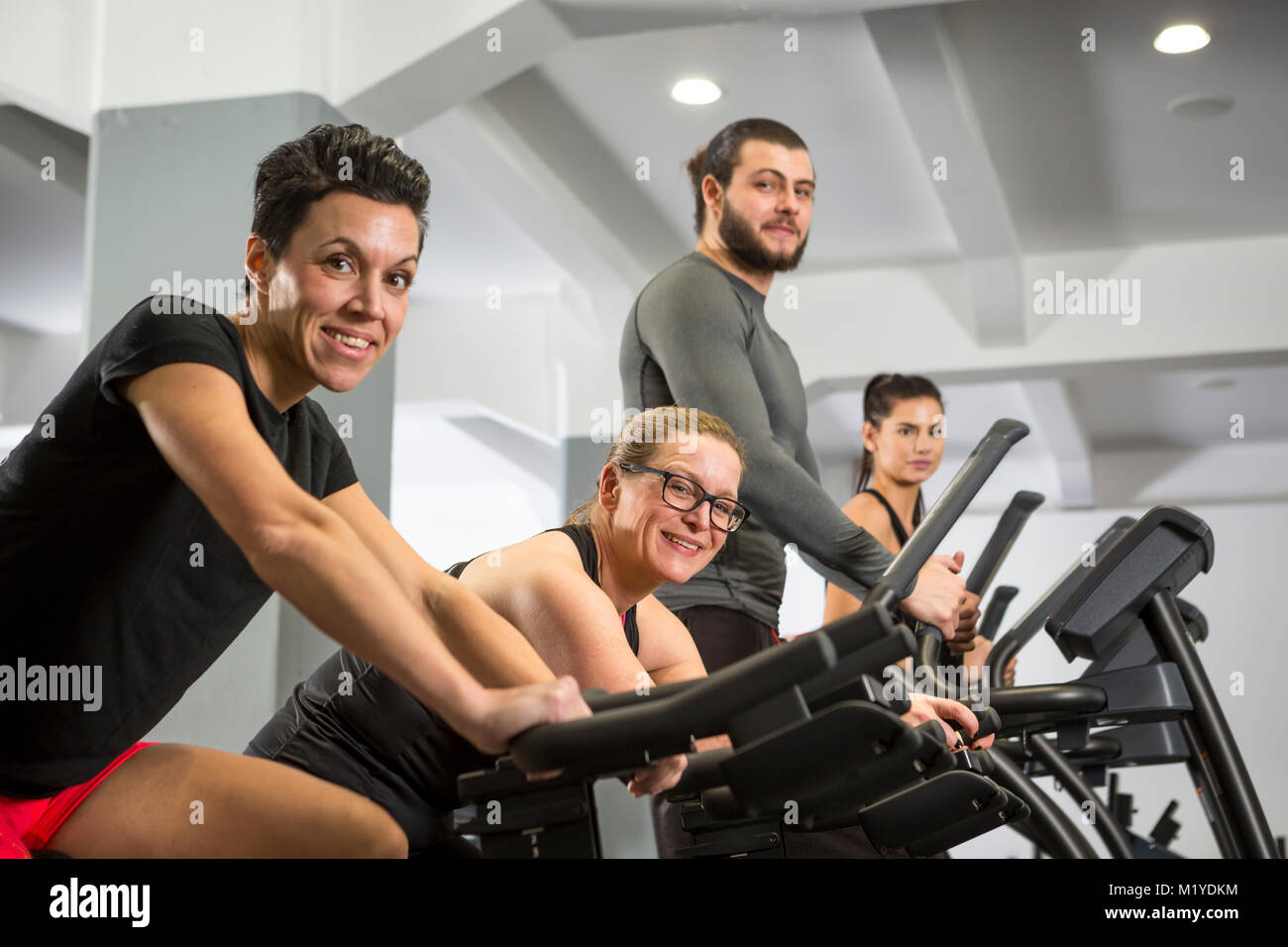Three women and one man training at a gym in cardio machines. They all have happy expressions. - Stock Image