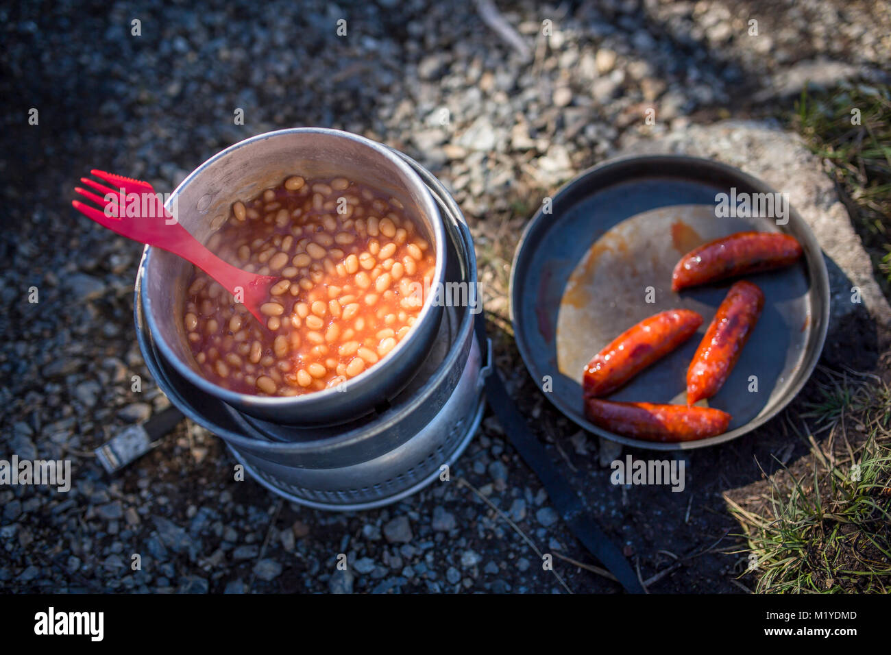Baked beans in a saucepan and sausages in a frying pan on a camping kitchen on the ground. Partly sun and partly - Stock Image