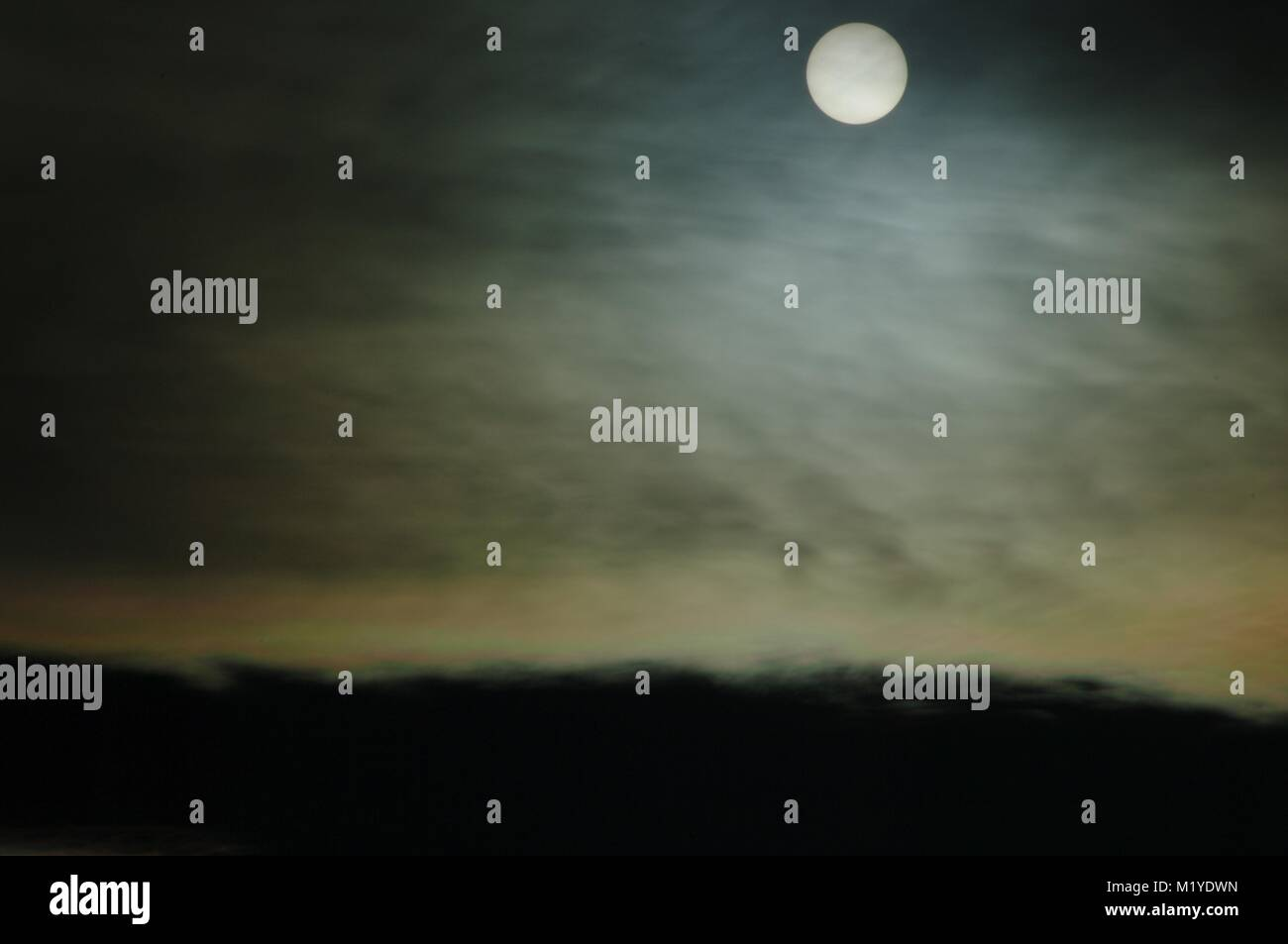 Weak Sun Shines through Maceral Altocumulus Clouds in a Spooky Abstract, Dark yet Glowing Effect. British Weather, - Stock Image
