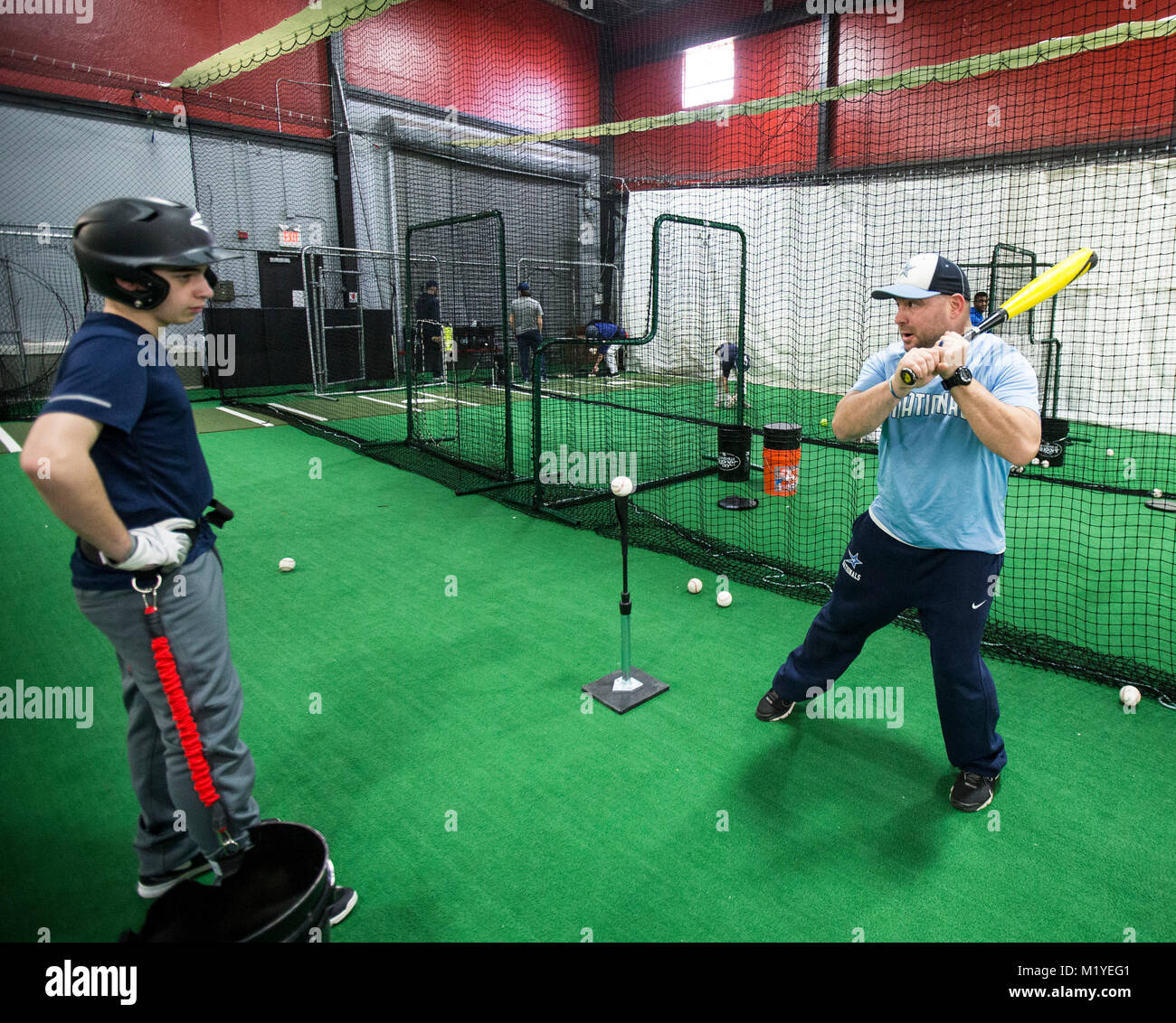 Baseball coach demonstrating proper hitting technique at an indoor training facility in New Jersey - Stock Image