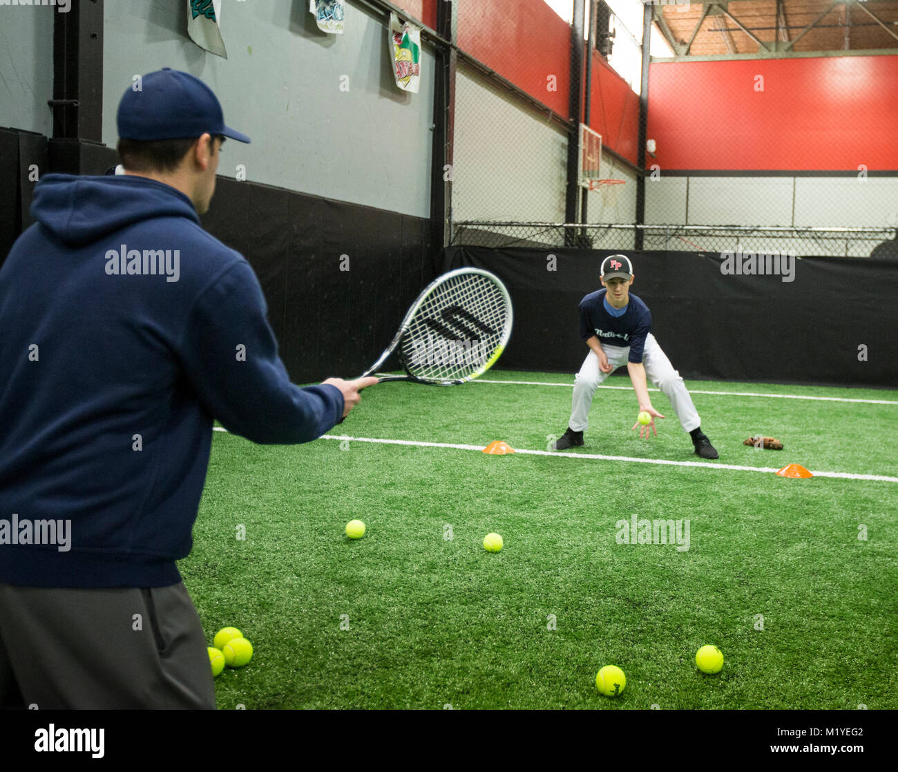 Baseball coach doing fielding drills at an indoor training facility in New Jersey - Stock Image
