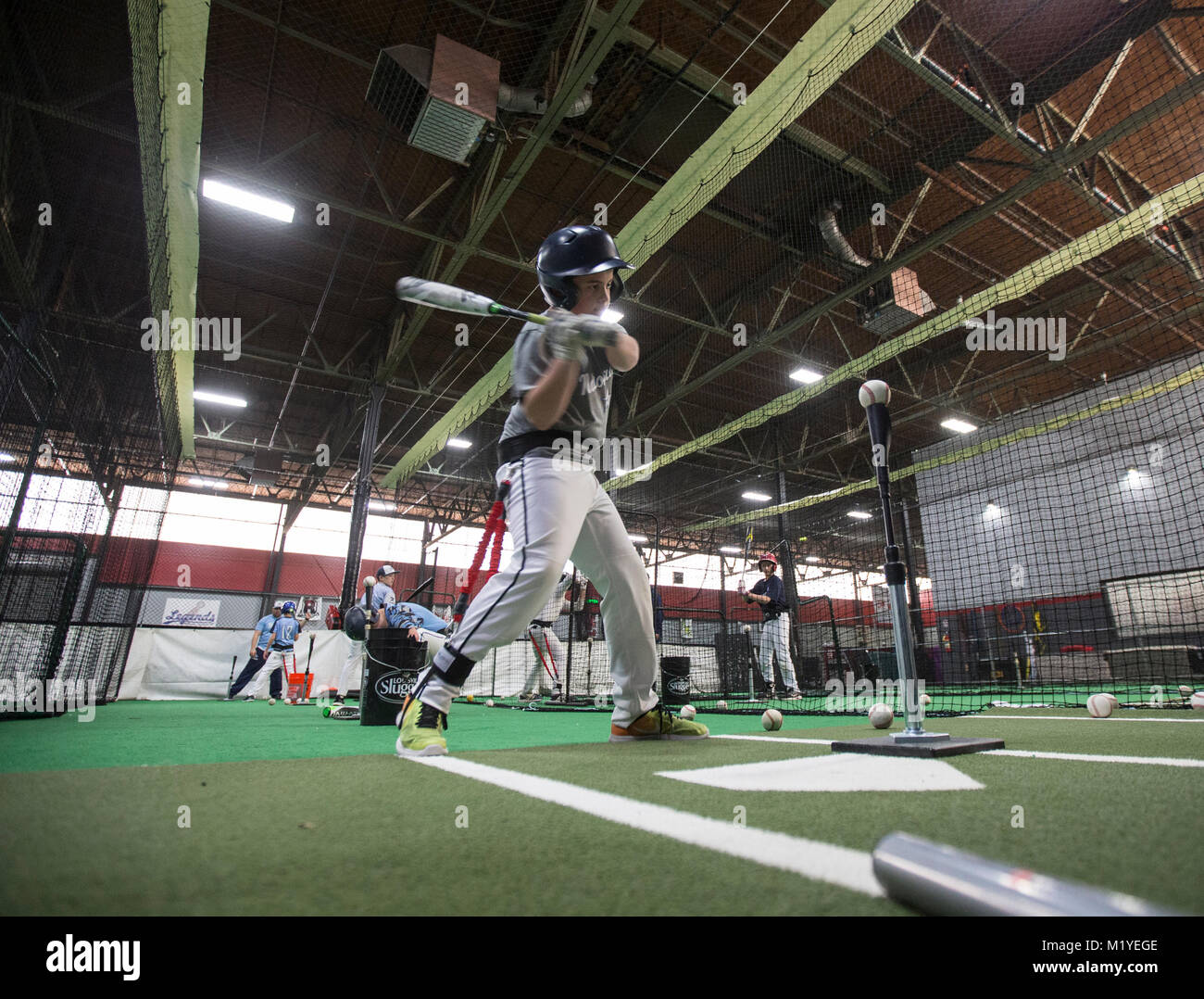 Baseball player practicing hitting at an indoor training facility in New Jersey - Stock Image