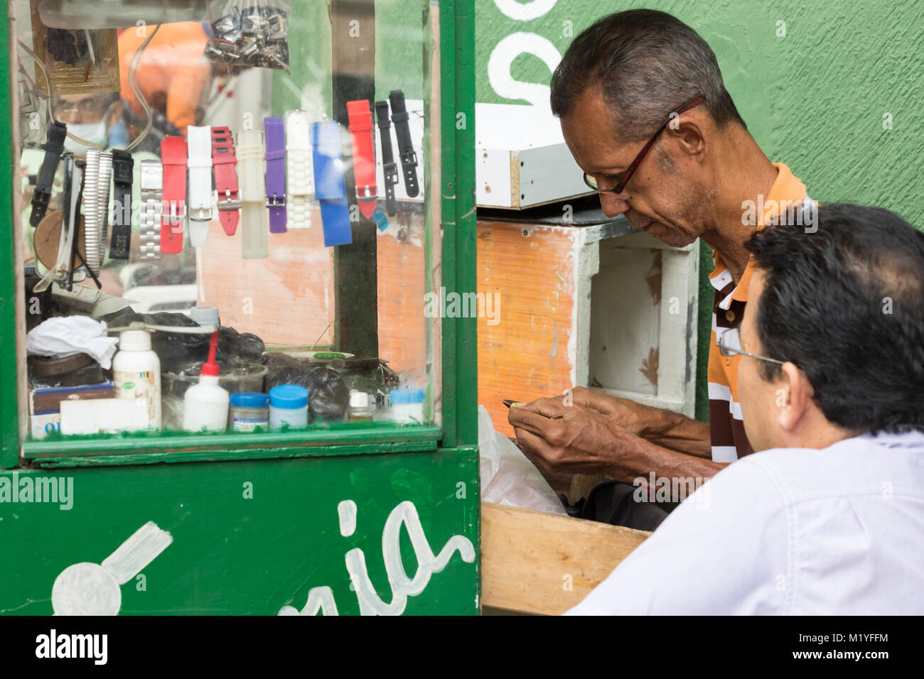 Cartagena, Colombia - January 24th, 2018: Portrait of a male watchmaker reparing a watch at the Parque de las Flores - Stock Image
