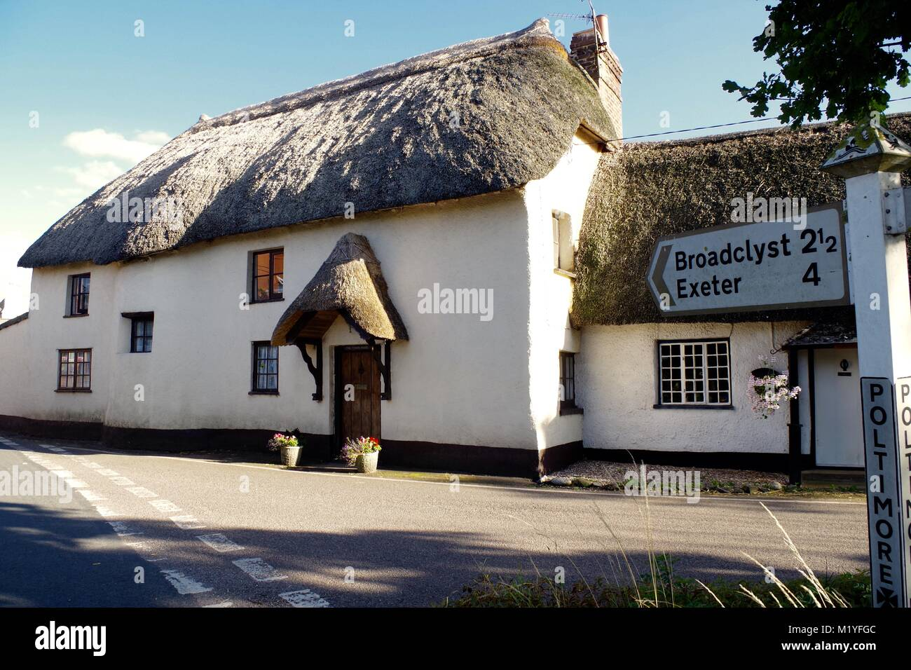Thatched Cottage and Old Road Signpost. Poltimore Village, Exeter, Devon, UK. August, 2016. - Stock Image