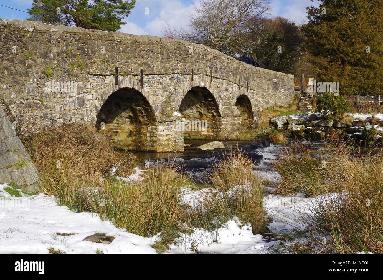 18th Century Granite Bridge over the East Dart River at Postbridge, Dartmoor National Park, Devon, UK. February, - Stock Image