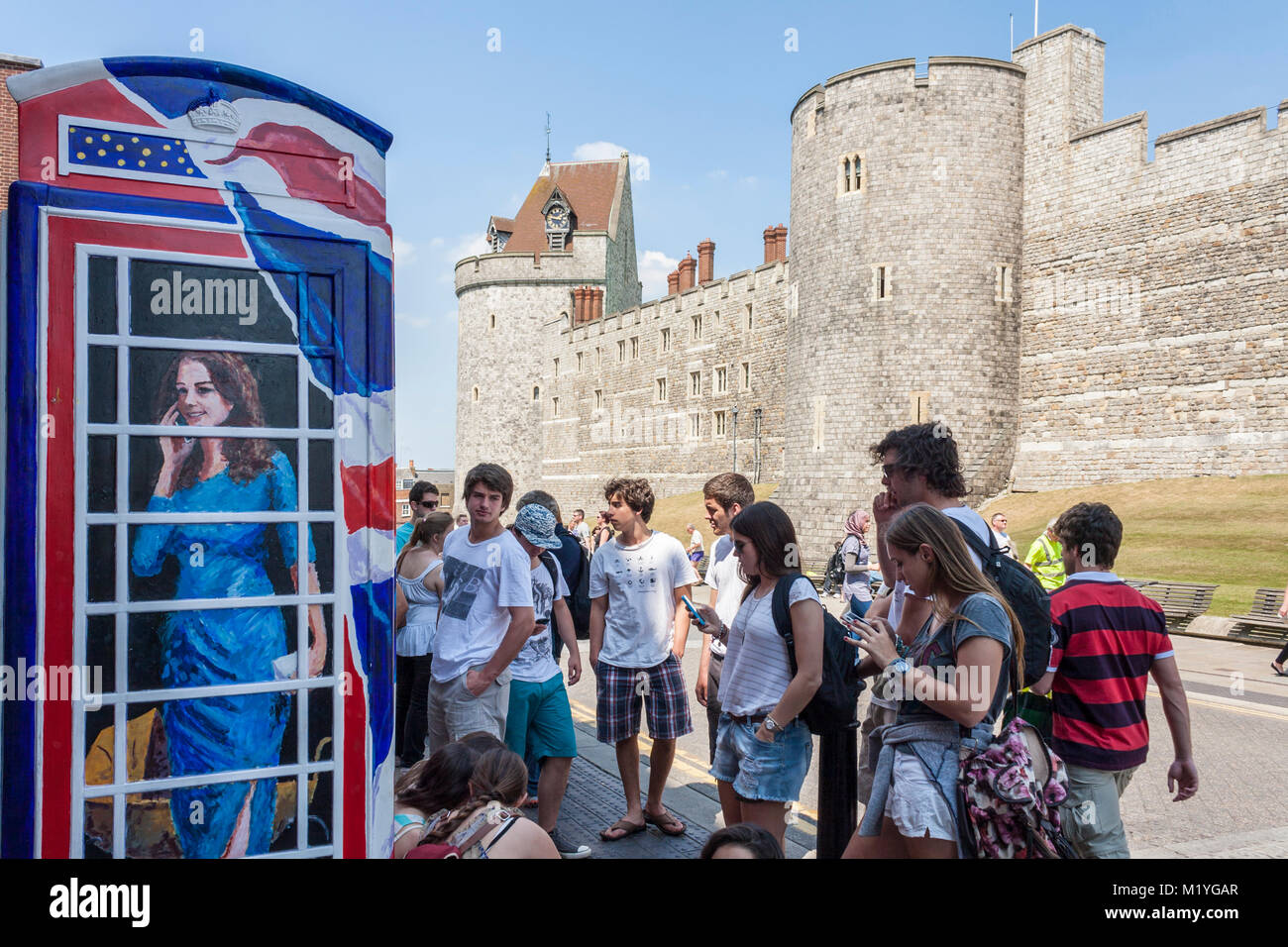 Teenage tourists look at mobile phones outside a traditional UK phone box painted with a portrait of Kate Middleton, - Stock Image