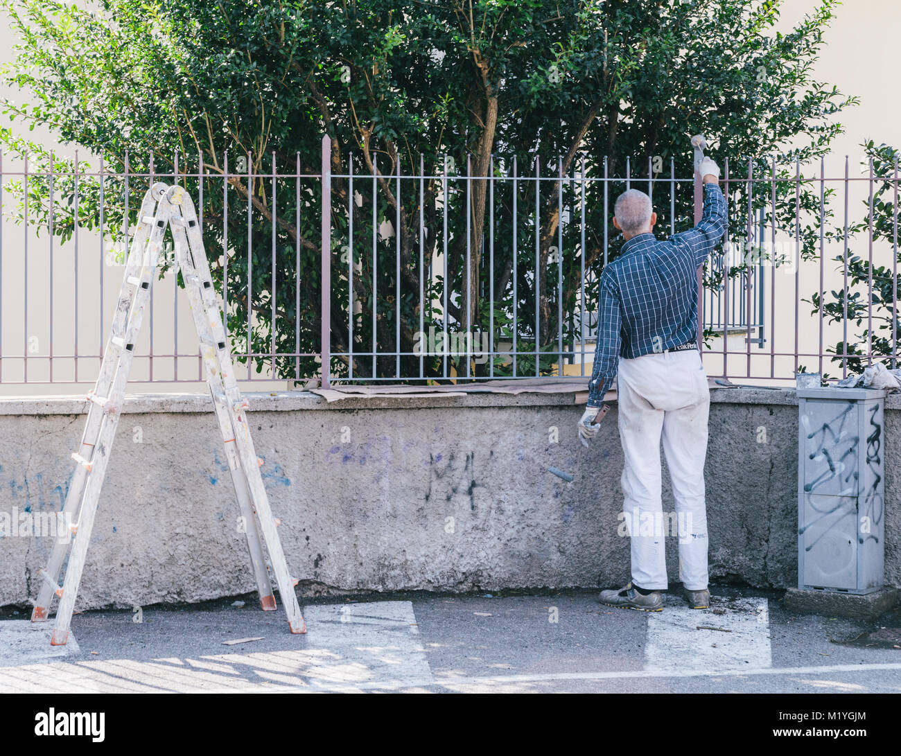 Older man painting a fence - Stock Image