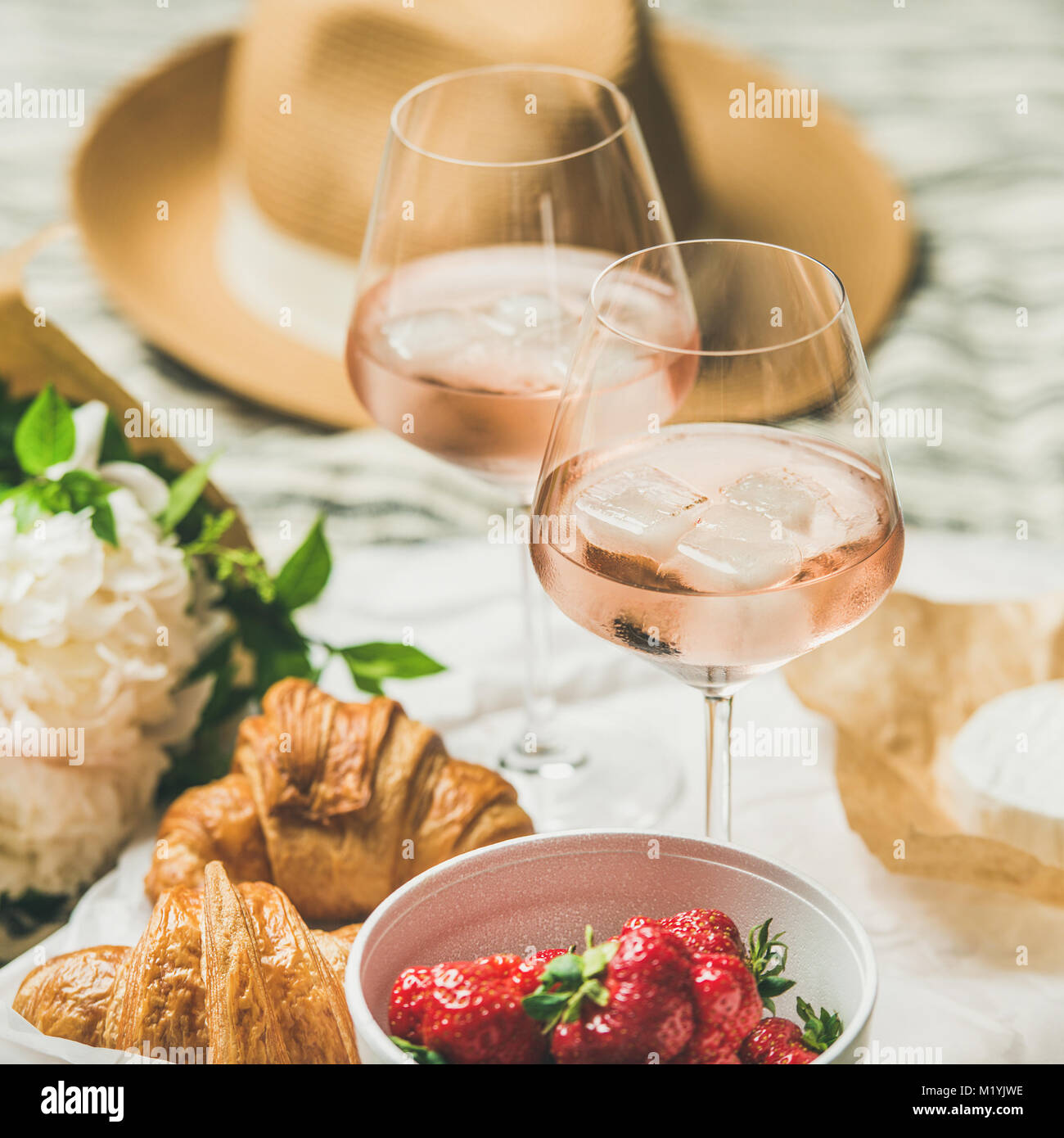 French style romantic summer picnic setting. Flat-lay of glasses of rose wine with ice, fresh strawberries, croissants, - Stock Image