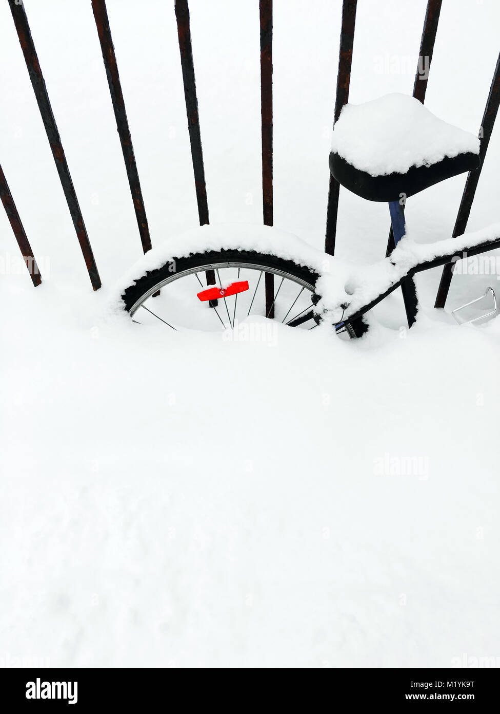Bicycle deep in snow, after snowstorm. Canadian winter. - Stock Image