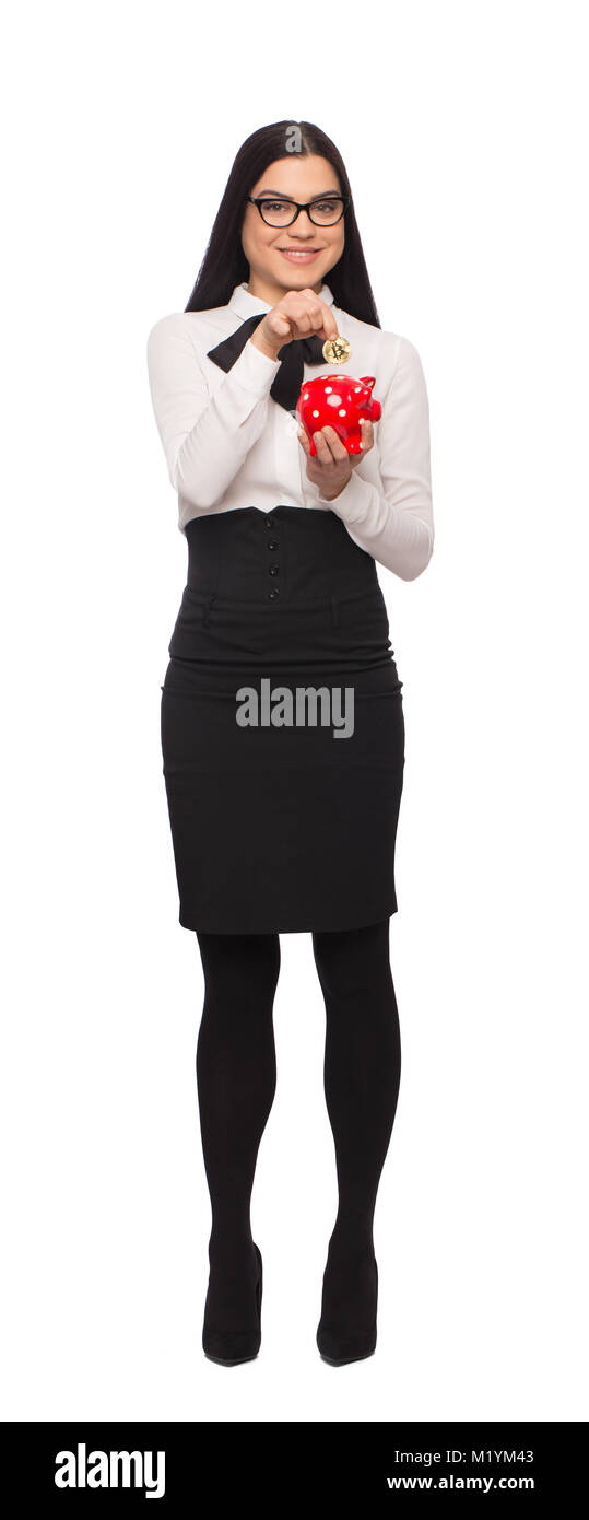 Young caucasian businesswoman in formal wear drop bitcoin into piggy bank, isolated on white - Stock Image