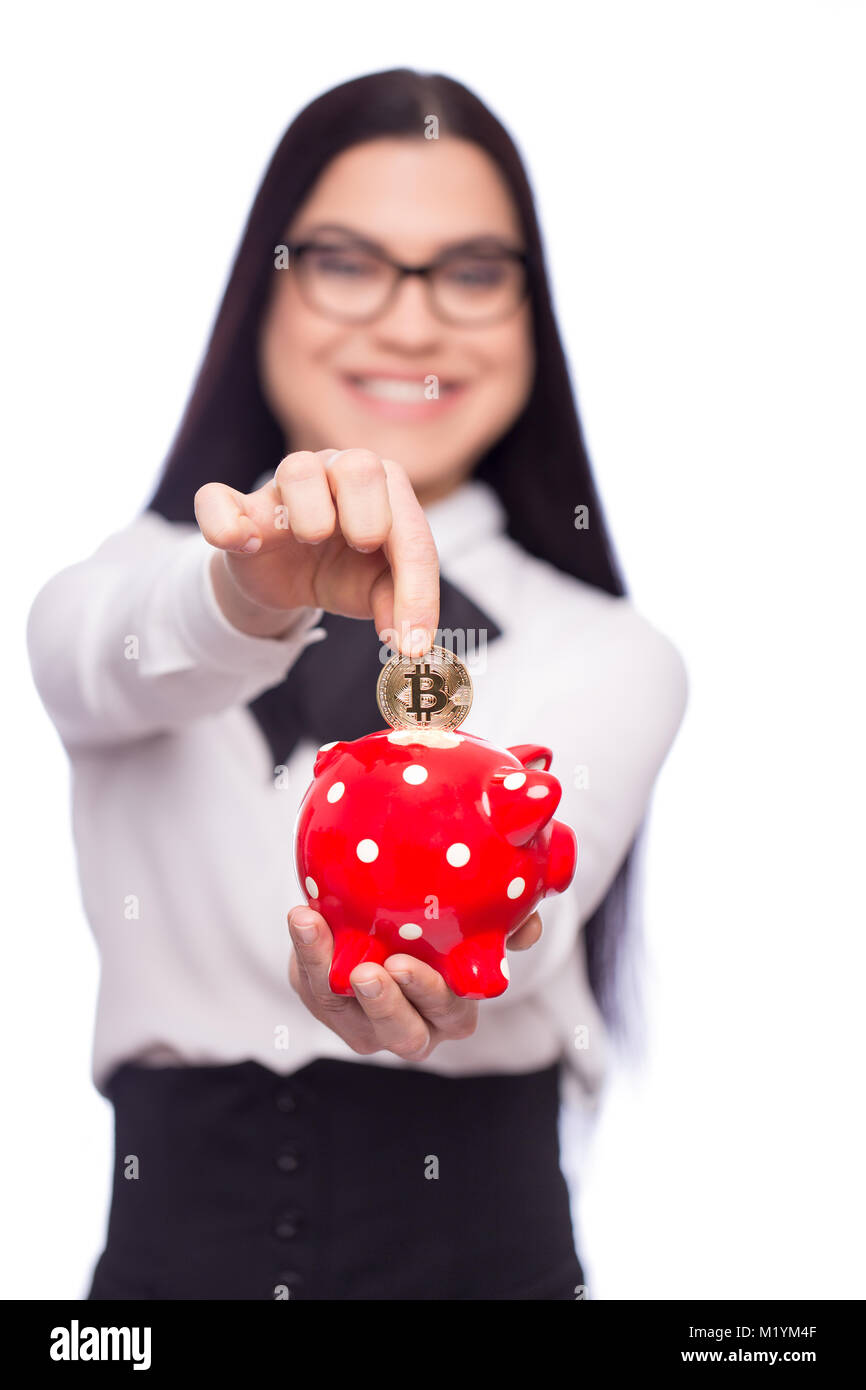 Happy smart young caucasian businesswoman in formal wear drop bitcoin into piggy bank, isolated on white, depth - Stock Image