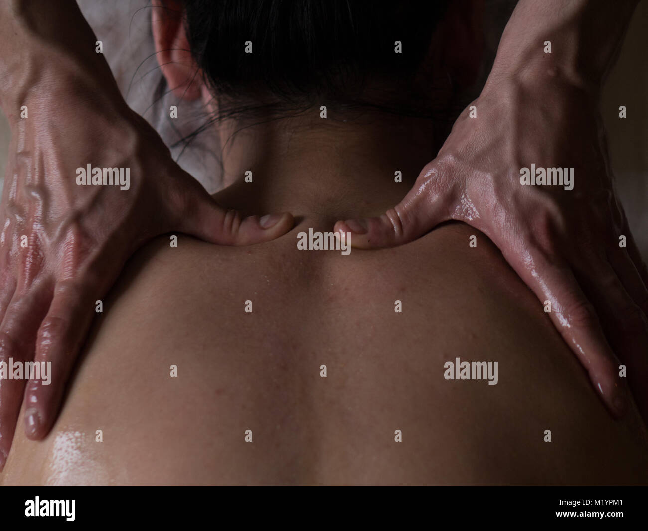 Ayurveda Massage concept. Beautiful young woman reciving relxing Massage from Professional Masseur. Close up - Stock Image
