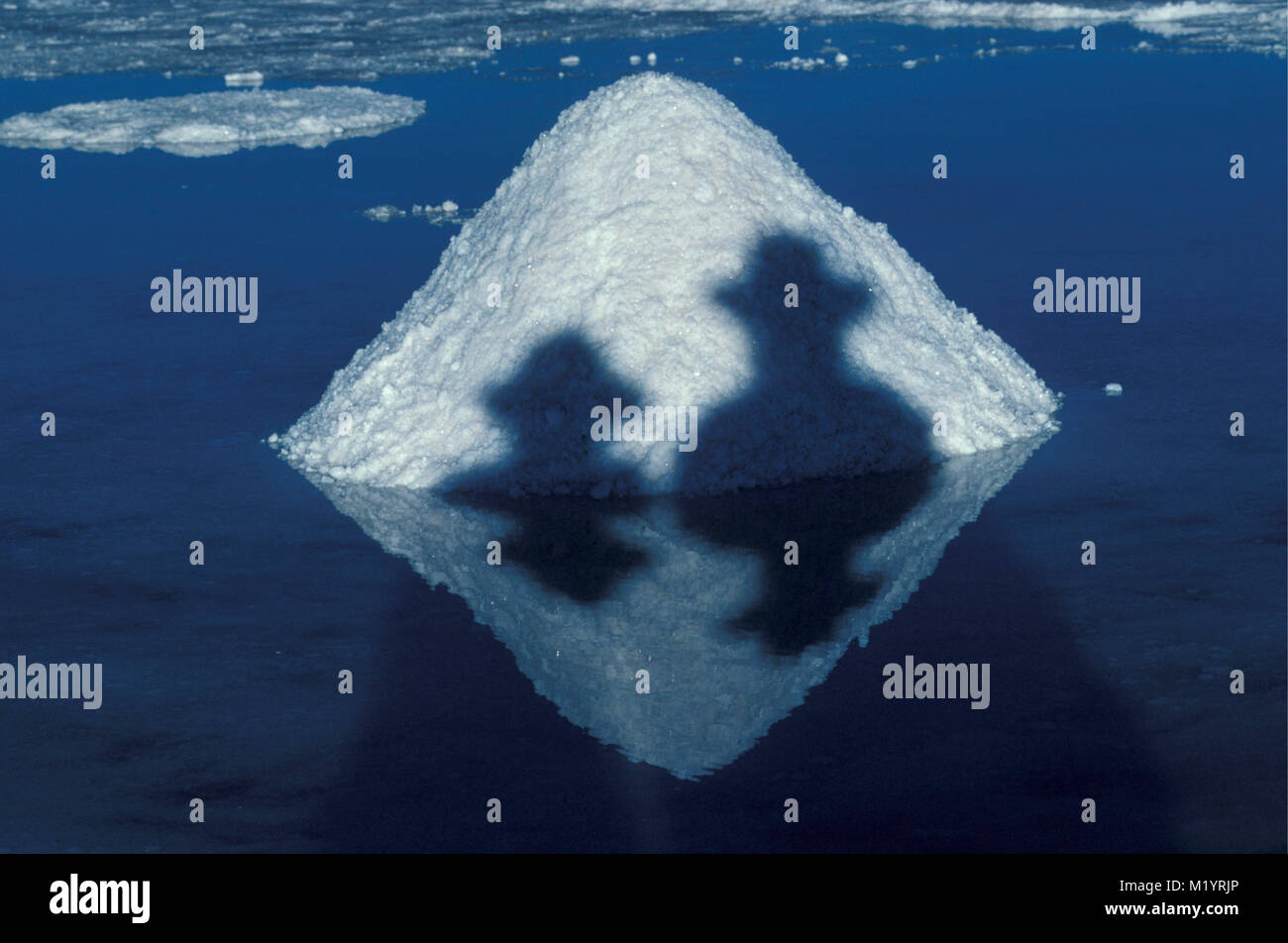 Bolivia. Uyuni. Salar de Uyuni. Salt industry in Uyuni salt lake. Salt harvesting.  Shadow of people with hat. Reflection. - Stock Image
