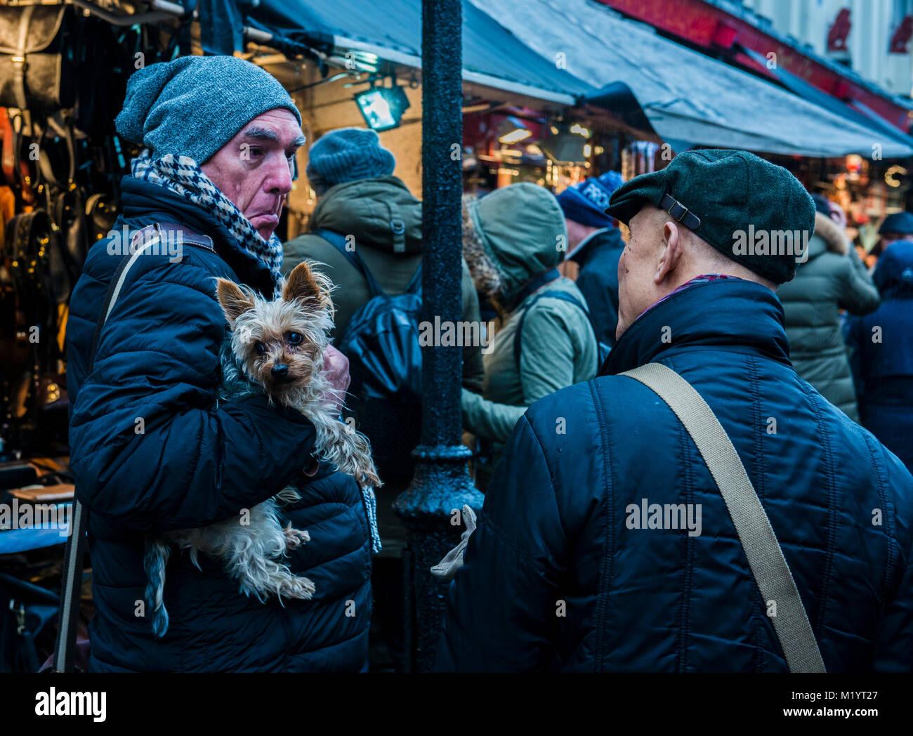 Two men face to face, one holding dog, Portobello, London, England - Stock Image