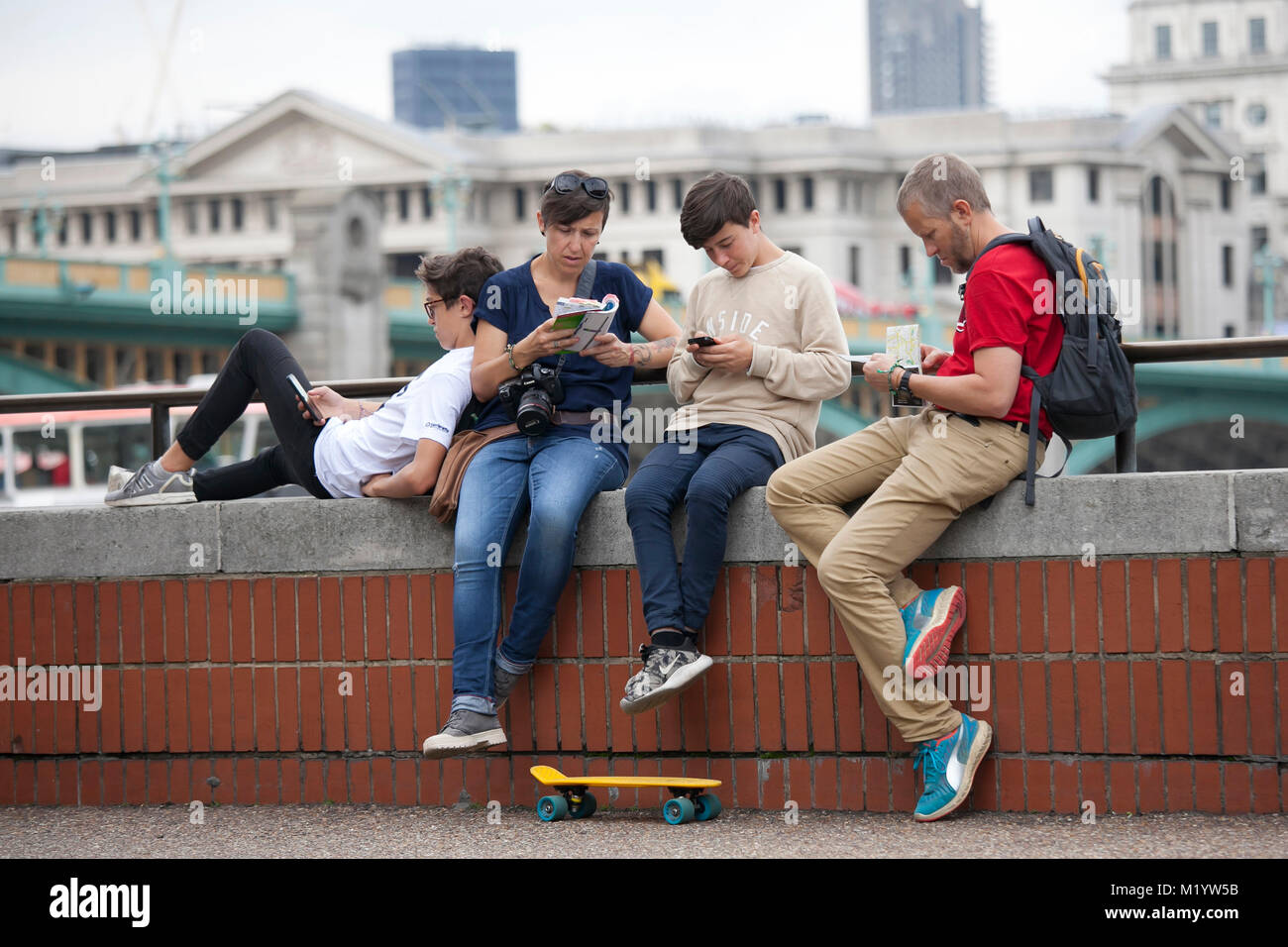 LONDON, ENGLAND - AUGUST 22, 2017 A family of tourists looking at a map against the background of the River Thames - Stock Image