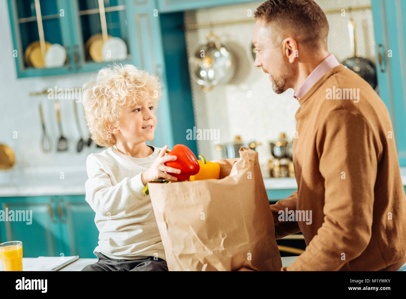 Cheerful cute boy looking at his father - Stock Image